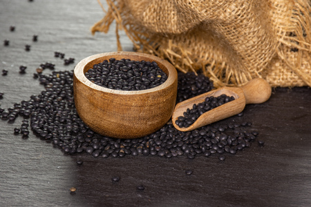 Composition lot of whole black lentils beluga variety with wooden bowl on grey stone Stok Fotoğraf