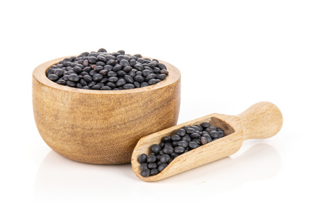 Lot of whole black lentils beluga variety bowl with wooden scoop isolated on white background Stok Fotoğraf