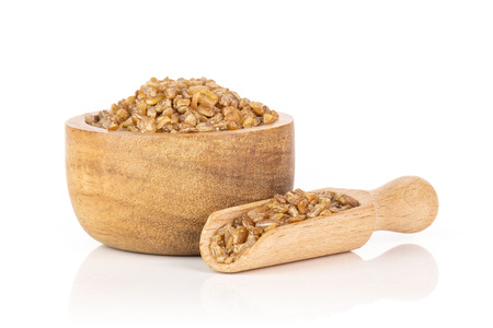 Lot of whole raw bulgur grains in a scoop with wooden bowl isolated on white background