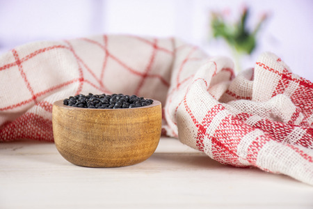 Lot of whole black lentils beluga variety towel with wooden bowl with red flowers on white