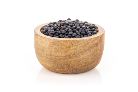 Lot of whole raw black lentils beluga variety with wooden bowl isolated on white background Stok Fotoğraf