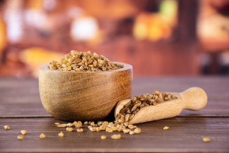 Lot of whole raw bulgur grains in a scoop with wooden bowl in a rustic kitchen Stock fotó