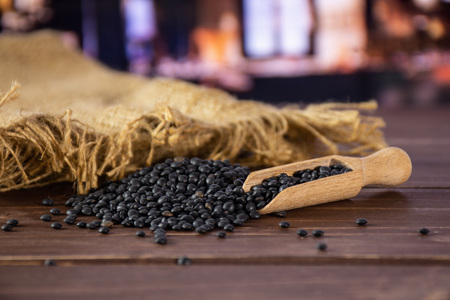 Lot of whole black lentils beluga variety jute with wooden scoop in a restaurant Stok Fotoğraf