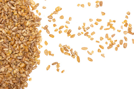 Lot of whole raw bulgur grains copyspace on left flatlay isolated on white background