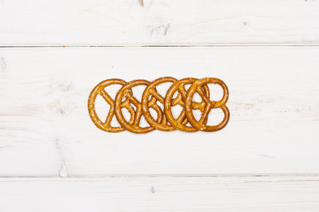 Lot of whole mini salted pretzels in a line flatlay on white wood
