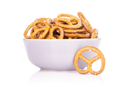 Lot of whole mini salted pretzels in a grey ceramic bowl isolated on white background