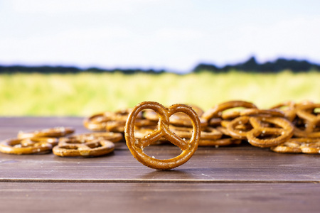 Lot of whole mini salted pretzels one is in a focus with green wheat field