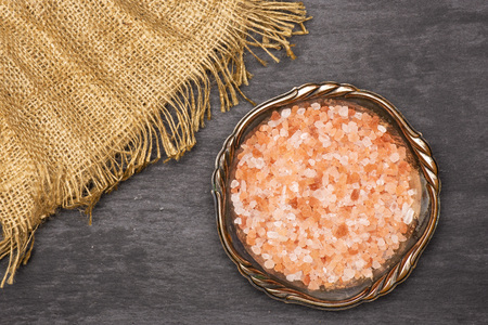 Lot of pieces of pink himalayan salt crystals in old iron bowl flatlay on grey stone