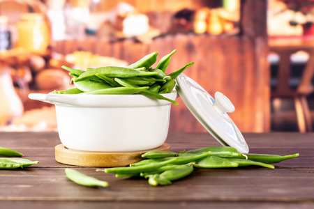 Lot of whole fresh green sugar snap pea with a stewpan in a rustic kitchen