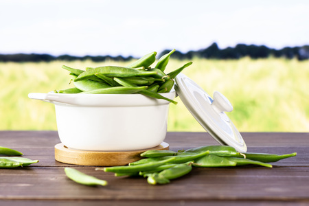 Lot of whole fresh green sugar snap pea with a stewpan in a green field