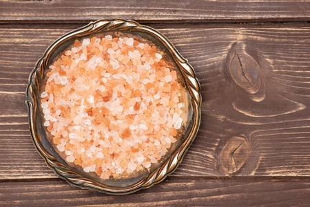 Lot of pieces of pink himalayan salt crystals in old iron bowl flatlay on brown wood