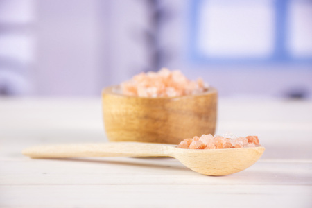Lot of pieces of pink himalayan salt crystals in a spoon with blue window in a kitchen