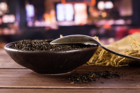 Lot of pieces of dry black tea earl grey in a grey ceramic bowl on jute cloth with silver spoon with restaurant in background