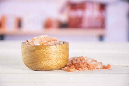 Lot of pieces of pink himalayan salt crystals in a wooden bowl in a white kitchen 스톡 콘텐츠