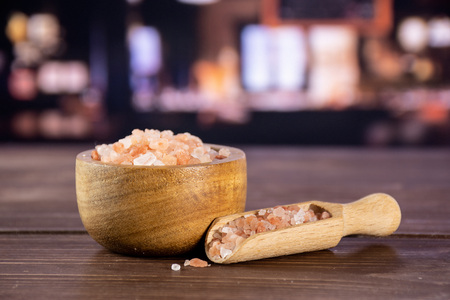 Lot of pieces of pink himalayan salt crystals in a wooden bowl in a restaurant 스톡 콘텐츠