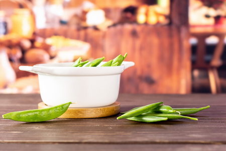 Lot of whole green sugar snap pea with a stewpan in a rustic kitchen