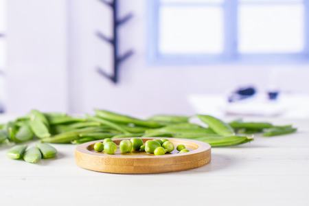 Lot of whole green sugar snap pea on bamboo plate with blue window in a white kitchen 스톡 콘텐츠