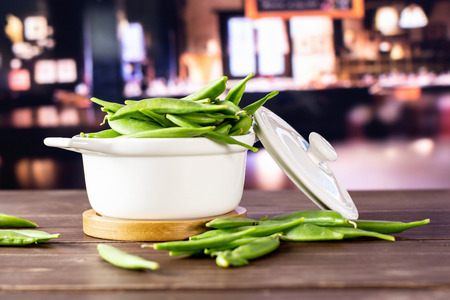 Lot of whole fresh green sugar snap pea with a stewpan in a restaurant 스톡 콘텐츠
