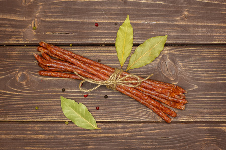 Lot of whole spicy salami stick tyrolini tied by jute with black pepper and bay leaf flatlay on brown wood 版權商用圖片