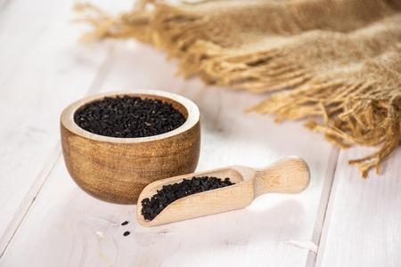 Lot de graines de cumin noir entières avec cuillère en bois, bol en bois et toile de jute sur bois blanc
