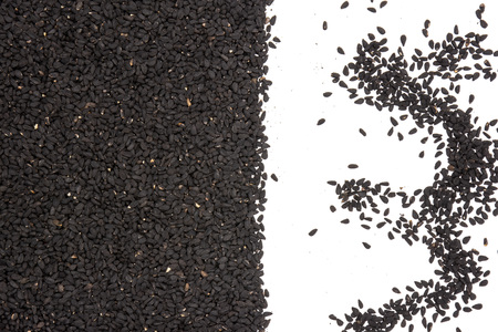 Lot of whole small black cumin seeds flatlay isolated on white background Imagens