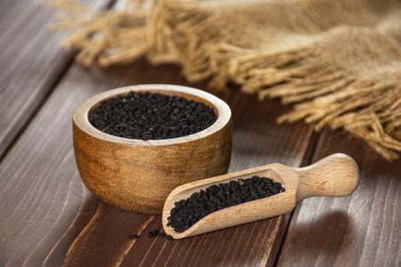 Lot de graines de cumin noir entières avec bol en bois, pelle en bois et toile de jute sur bois marron Banque d'images