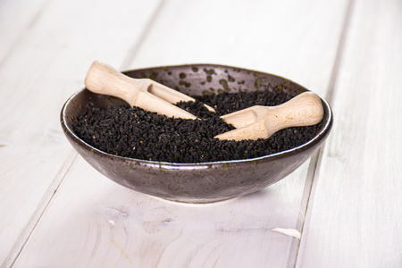 Lot of whole black cumin seeds in a grey ceramic bowl with wooden scoop on white wood