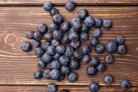 Lot of whole fresh sweet purple blueberry american flatlay on brown wood