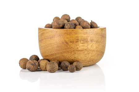 Lot of whole dry brown allspice berries with wooden bowl isolated on white background