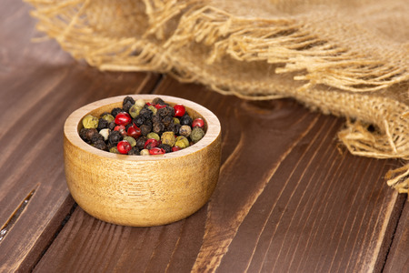 Lot of whole peppercorns of four colors with wooden bowl on jute cloth on brown wood