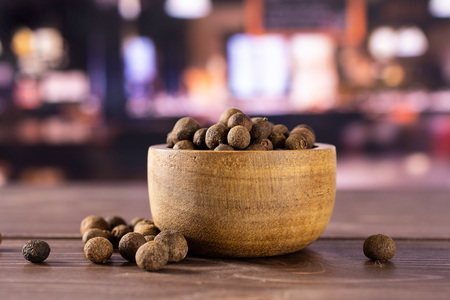 Lot of whole dry brown allspice berries with wooden bowl with restaurant in background Standard-Bild