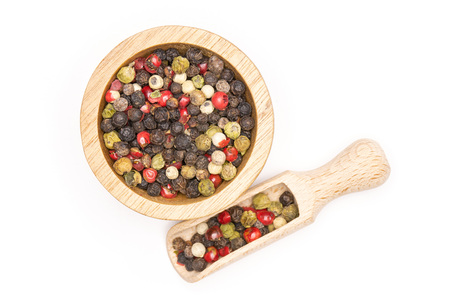 Lot of whole peppercorns of four colors with wooden bowl and wooden scoop flatlay isolated on white background Stock Photo