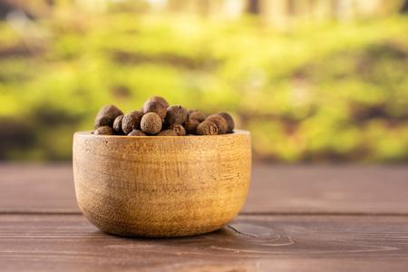 Beaucoup de baies de piment de la Jamaïque brunes sèches entières avec bol en bois avec forêt en arrière-plan