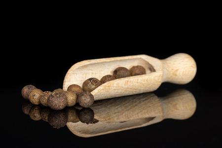 Beaucoup de baies de piment de la Jamaïque brunes sèches entières avec une cuillère en bois isolée sur verre noir Banque d'images