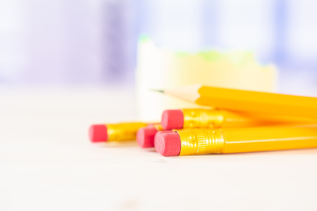 Group of five whole yellow pencil one is sharpened with a sticker roll with blue window in background