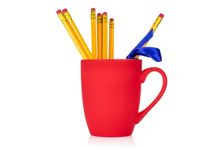 Group of seven whole yellow pencil tied by ribbon in a red cup isolated on white background 版權商用圖片