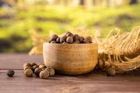 Lot of whole dry brown allspice berries with wooden bowl on jute cloth with forest in background 스톡 콘텐츠