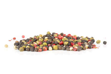 Lot of whole peppercorns of four colors isolated on white background