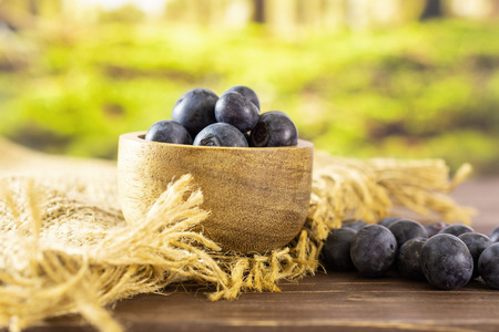 Lot of whole fresh sweet purple blueberry american on jute cloth with wooden bowl with forest in background Stock Photo
