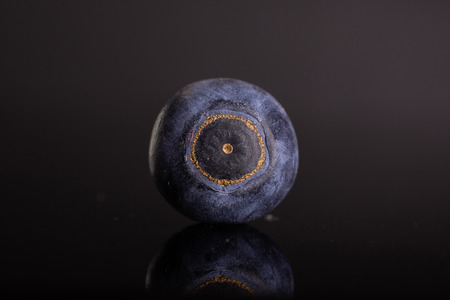 One whole fresh sweet purple blueberry american isolated on black glass