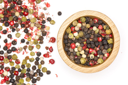 Lot of whole peppercorns of four colors with wooden bowl flatlay isolated on white background