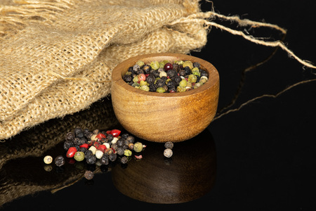 Lot of whole peppercorns of four colors with wooden bowl on jute cloth isolated on black glass Banque d'images
