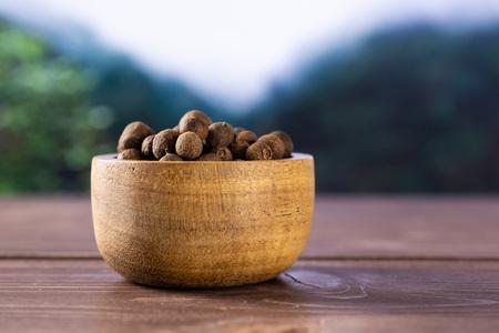 Beaucoup de baies de piment de la Jamaïque brunes sèches entières avec un bol en bois jungle asiatique en arrière-plan