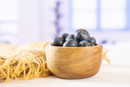 Lot of whole fresh sweet purple blueberry american on jute cloth with wooden bowl with blue window in background
