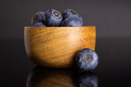 Lot of whole fresh sweet purple blueberry american with wooden bowl isolated on black glass Imagens