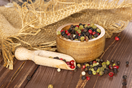 Lot of whole peppercorns of four colors with wooden bowl on jute cloth with wooden scoop on brown wood