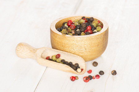 Lot of whole peppercorns of four colors with wooden bowl and wooden scoop on white wood Stock Photo