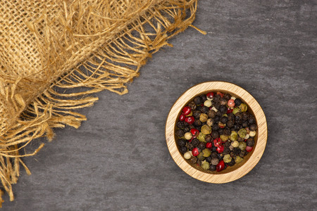 Lot of whole peppercorns of four colors with wooden bowl on jute cloth flatlay on grey stone Stock Photo