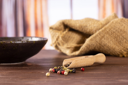 Lot of whole peppercorns of four colors on jute cloth with wooden scoop in a grey ceramic bowl with silk curtains behind Banque d'images