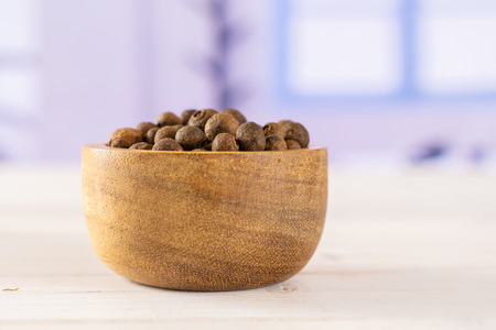 Lot of whole dry brown allspice berries with wooden bowl with blue window in background Standard-Bild - 119677973